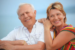 Smiling elderly married couple on veranda. Near seacoast Stock Image