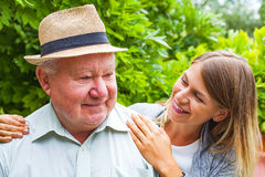 Elderly care outdoor. Smiling elderly men with beautiful young granddaughter posing in the park Royalty Free Stock Image