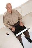 Smiling elderly senior man with laptop stock images