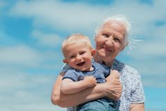 Elderly woman with a baby. Smiling elderly senior women with a baby Royalty Free Stock Photography