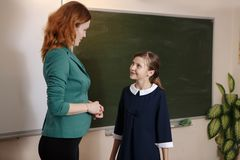 Smiling elderly teacher near the chalkboard asking student at the math lesson royalty free stock photo