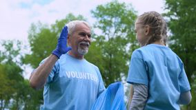 Smiling elderly volunteer with granddaughter collecting garbage giving high five. Stock footage stock video