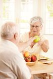 Smiling elderly wife handing apple to husband Stock Images