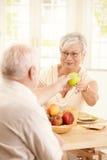 Smiling elderly wife handing apple to husband