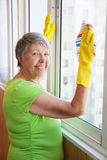 Smiling elderly woman cleaning a window Stock Images