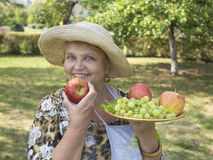 Smiling elderly woman in the country with apples.. Smiling elderly woman in the country with apples and grapes. August Royalty Free Stock Photography