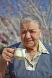 Smiling elderly woman drinking coffee Stock Photos