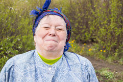 Smiling elderly woman in a headscarf in your garden Royalty Free Stock Photos