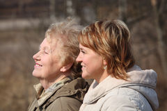 Smiling elderly woman and her daughter in profile Royalty Free Stock Images