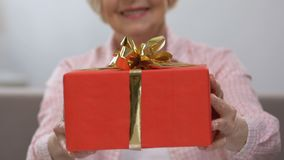 Smiling elderly woman holding gift box, family holiday celebration, happiness. Stock footage stock video