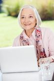 Smiling Elderly Woman Looking Away While Using Stock Photo