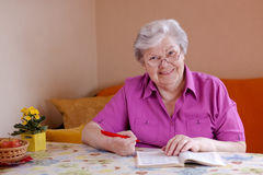 Smiling elderly woman looks to the viewer. Elderly woman with reading glasses sitting on the couch and smiles royalty free stock photo