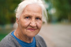 Smiling elderly woman. Portrait of a smiling elderly woman. A photo on the nature background royalty free stock image