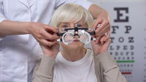 Smiling elderly woman putting on phoropter, choosing proper lens diopter, test. Stock footage stock video