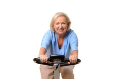 Smiling elderly woman riding an exercise bicycle Stock Photography