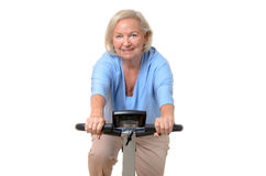Smiling elderly woman riding an exercise bicycle Royalty Free Stock Photos