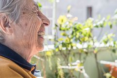 Smiling elderly woman sitting in the balcony having conversation with her family. royalty free stock photography
