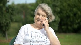 Smiling elderly woman talking using a smart phone stock footage