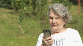 Smiling elderly woman talks using a smart phone stock video footage