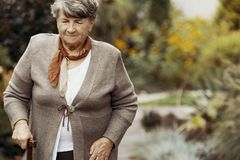 Smiling elderly woman with walking stick in the middle of nature royalty free stock photos
