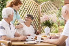 Smiling elderly woman eating breakfast with friends and her care royalty free stock images