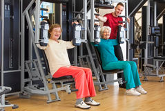 Smiling Elderly Women at the Gym with Instructor. Smiling Elderly Women Working Out at the Fitness Gym with their Male Instructor, Looking at the Camera Stock Images