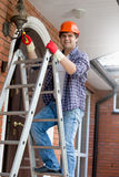 Smiling electrician in hardhat climbing the stepladder Royalty Free Stock Image
