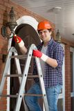 Portrait of smiling electrician in plastic protective helmet standing on stepladder. Smiling electrician in plastic protective helmet standing on stepladder Royalty Free Stock Images