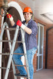 Smiling electrician standing on stepladder and repairing outdoor Royalty Free Stock Images