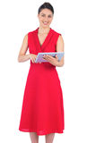 Smiling elegant brunette in red dress holding tablet pc Royalty Free Stock Photography