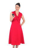 Smiling elegant brunette in red dress looking at her smartphone Stock Photo