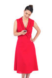 Smiling elegant brunette in red dress sending text message Royalty Free Stock Photo
