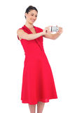 Smiling elegant brunette in red dress taking picture Royalty Free Stock Photography