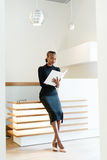 Smiling elegant business woman wearing black dress and beige shoes in light office looking at her agenda, full length portrait Stock Photos