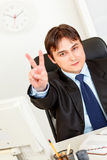 Smiling elegant businessman showing victory Stock Photos
