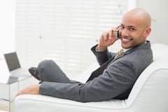 Smiling elegant businessman using cellphone on sofa at home Royalty Free Stock Photography