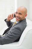Smiling elegant businessman using cellphone on sofa at home Stock Photography