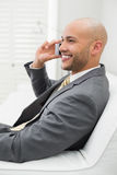 Smiling elegant businessman using cellphone on sofa at home Royalty Free Stock Photo