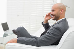 Smiling elegant businessman using cellphone on sofa at home Stock Images