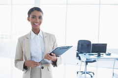 Smiling elegant businesswoman holding clipboard Royalty Free Stock Photo