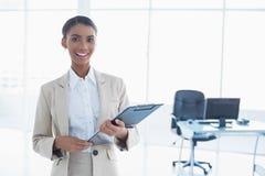 Smiling elegant businesswoman holding clipboard Royalty Free Stock Photo