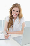 Smiling elegant businesswoman writing document at desk Stock Photo