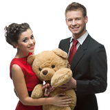 Smiling elegant couple holding big soft toy Stock Photo