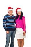Smiling elegant couple in Santa hats royalty free stock photography