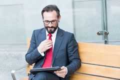 Smiling elegant entrepreneur reading news while using tablet outdoors royalty free stock images