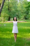 Smiling elegant girl standing in forest on sunny summer day Royalty Free Stock Photo