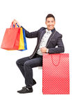 A smiling elegant guy posing with shopping bags in his hand Royalty Free Stock Image