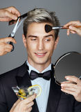 Smiling elegant man and many hands making different beauty salon services Stock Photo
