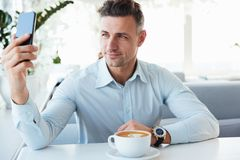 Smiling elegant mature man resting alone in cafe with cup of caf. Feine beverage and making selfie or photographing on black smartphone Stock Images
