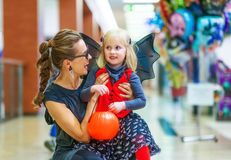 Smiling elegant mother and daughter on Halloween at mall. Trick or Treat. Portrait of smiling elegant mother and daughter in bat costumes on Halloween at the Royalty Free Stock Photo